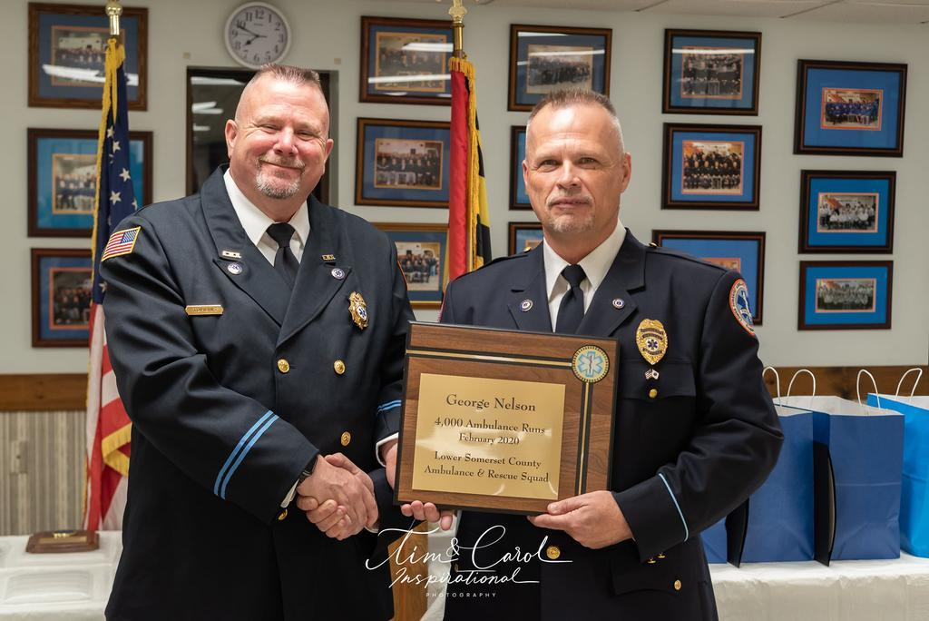 Captain Matt Tomlins presents President George Nelson with a plaque for running over 4000 calls.